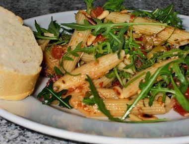 Für den mediterranen Pennesalat die Nudeln al dente kochen und erkalten lassen. Cocktailtomaten, Champingons, Zwiebel und Mozzarella zerkleinern