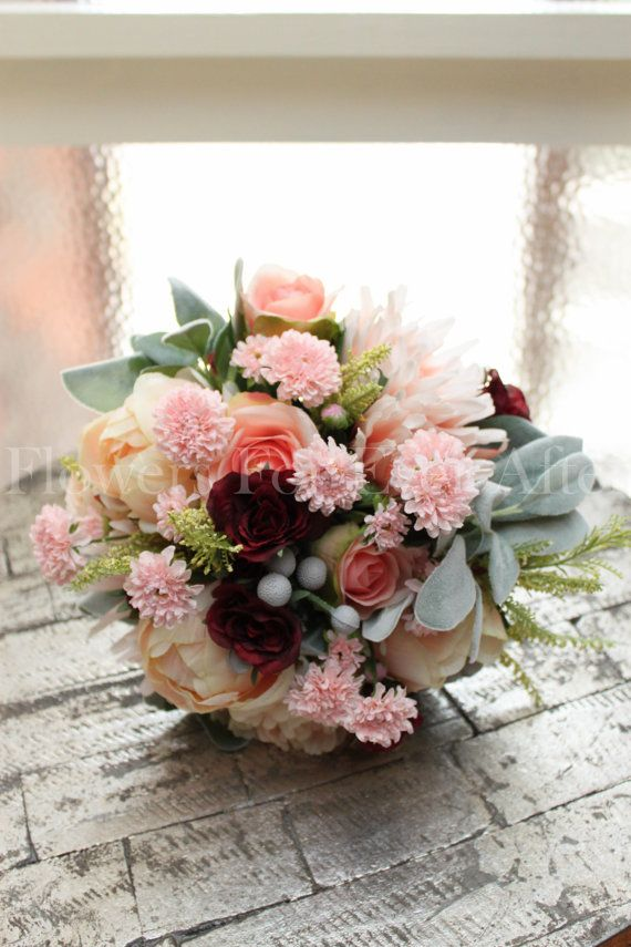 Classic bridal colours in a textured romantic posy.  Features champagne apricot peony buds, apricot pink spider dahlia, apricot frill peony, coral roses, pink chrysanthemum, brunia berries and lamsea foliage with splashes of small burgundy roses to lift the bouquets colours.  Bouquet handle is finished with champagne satin and pearl studs.  Measuring approximately 26cm across (10 inches). A matching bridesmaid posy is available in a separate listing.   Worldwide Postage Available  Maria +61…
