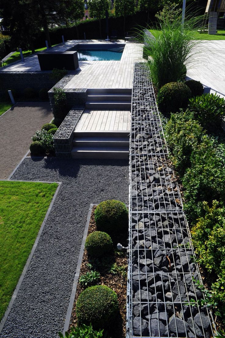 Gabion retaining wall between the house and pool that continues across the  garden to the fence.