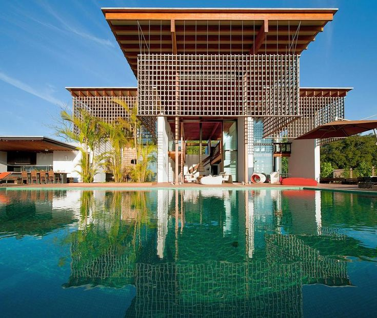 OASI TROPICALE IN BRASILE: VISTA PISCINA Maestosa, questa villa in Brasile, completamente aperta, affaccia su una grande piscina dal fondo verde acqua ed è schermata dal sole da una serie di strategici brise-soleil. Foto © Rómulo Fialdini