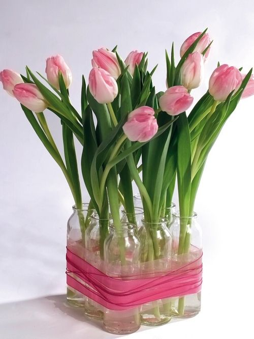 What a cool way to make a centerpiece out of a bunch of tulips and some small jars or vases. These look like they might be French milk bottles...