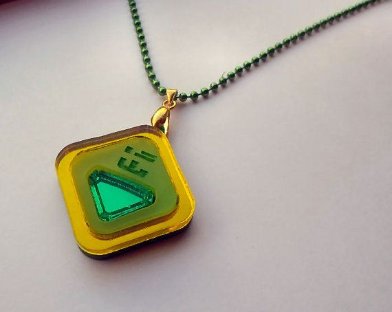 Based off of the homeworld gems little angry slice of pie and technological savvy Peridot (but dont call her cute!) in the show Steven Universe. This pendant is laser carved and cut out of reflective and opaque acrylics. Its mirror quality and shine captures light beautifully! Her love for technology and information gathering shows with her engraved screen icons placed above her Peridot gem. You will receive one necklace connected with a 16 green chain. The pendant measures 1.5 x 1.5…