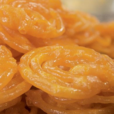 Jalebi: small, bright yellow, web-shaped cakes similar to funnel cakes. They are popular celebration and street cakes in Bangladesh, Nepal, Pakistan, and India. Soaking them in saffron syrup and then drying them gives the cakes a crispy outer shell.