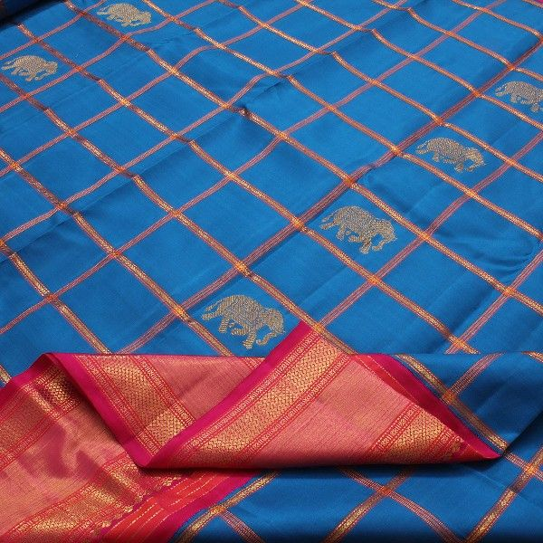 Majestic gold elephants strut in alternate squares, against the backdrop of a deep blue sky. Rani pink and gold checks add lustre to this azure blue #sari, whilst the rani pink, gold and orange border adds a hint of opulence. The vibrant pink pallu is a shimmer of gold with rudraksh, annams and yali motifs. A hot pink blouse with running border completes the look of this #Sarangi Kanjivaram. For such beautiful blues, visit Sarangi. Code 580125592.