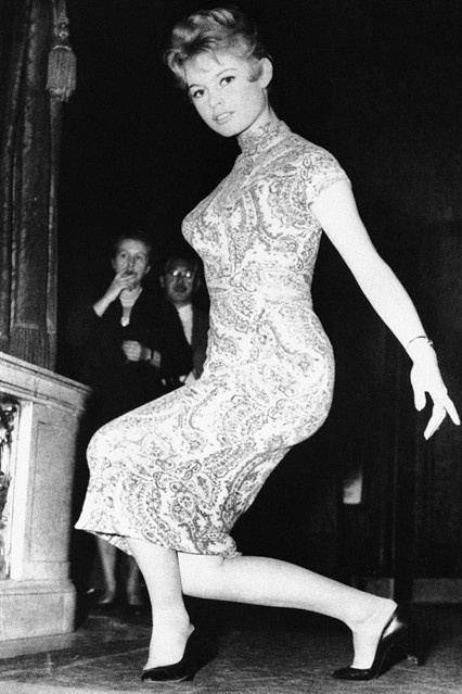OCTOBER 1956 – Ahead of her presentation to Queen Elizabeth II, Bardot spent time practicing her curtsey in a Chinese-inspired dress. Photo By PA Photos