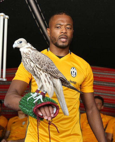 Juventus' French defender Patrice Evra poses with a falcon after a training session in Doha on December 21, 2016, two days before the Italian Super Cup final football match between Juventus and AC Milan in the Qatari capital.  / AFP / KARIM JAAFAR