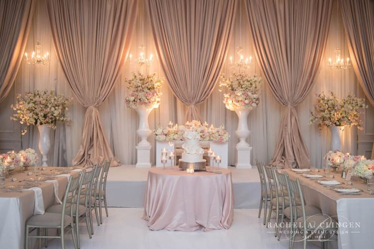 Soft pink and cream wedding backdrop by Rachel A. Clingen including beautiful white lacquer urns filled with flowers and cherry cherry blossoms.