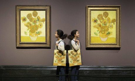 Identical twins pose by two versions of Van Gogh's sunflower paintings at the National Gallery. Photograph: Leon Neal/AFP/Getty Images