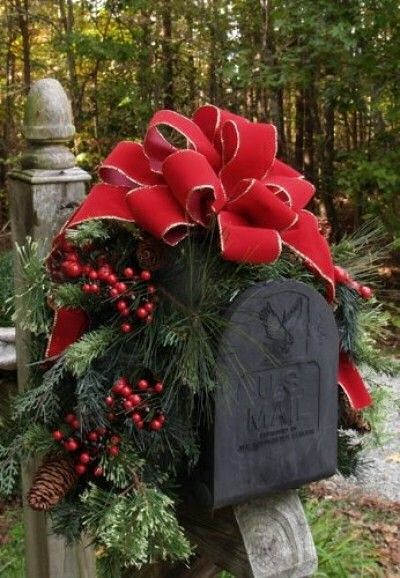 Drape a garland over a black mail box and attach a big red wire rimmed bow for a festive look.