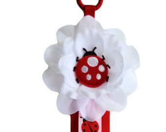 Handmade matching headband and hair clip holder. The holders are crafted using high quality grosgrain ribbon. The headband holder features 10 loops and both measure 20 in length. The top of the holders feature a 1.5 ribbon wrapped metal ring for easy hanging and embellished with a 4 white flower with a puffy ladybug in the center. Excellent for storing all your hair accessories