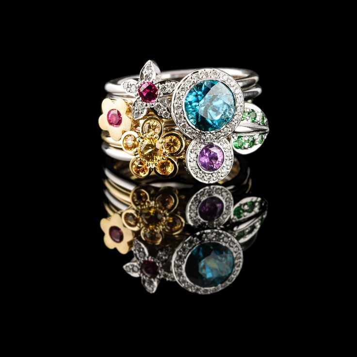 A stack of six of our Flower rings set with sapphires, tsavorites, diamonds and the big blue stone is a Zircon which is just the most amazing gemstone.