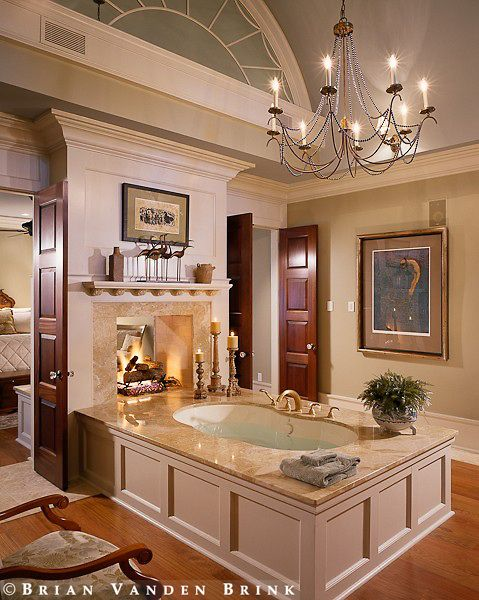 Bathtub flanked by beautiful doors and a see-through fireplace