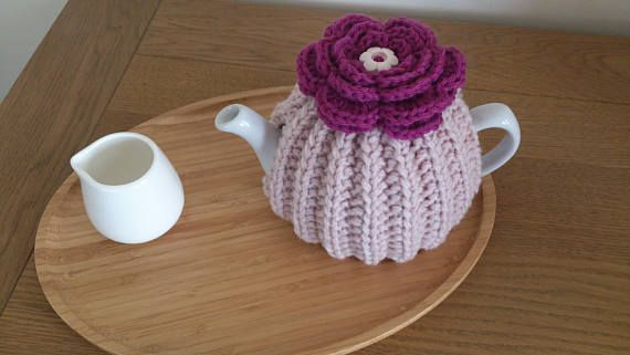 Pink  hand knitted tea cosy with crochet flower top and