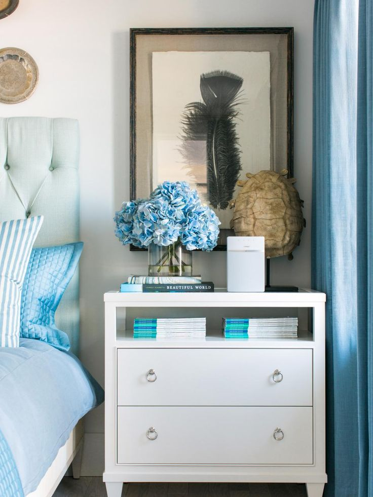 On the right of the bed, a two drawer chest with a shelf is topped with framed feather art print. The surface hold books for reading and other essentials for guests.