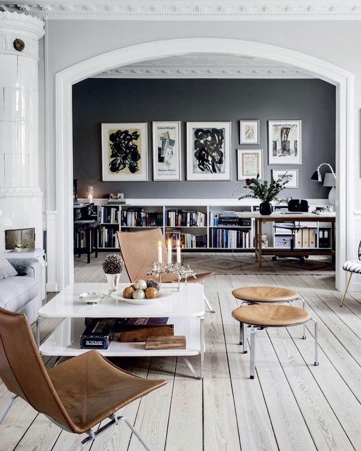 Juego de grises para destacar las molduras de esta casa reformada. Suelo de madera y muebles de piel en su color natural.