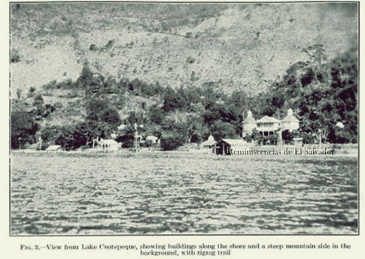 1925, vista desde el lago Coatepeque, mostrando edificios a lo largo de la costa y un lado empinado de la montaña en el fondo con el sendero en zig zag