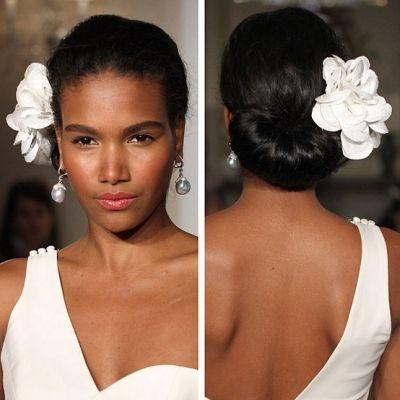 Elegant African American Formal Bun Topped with a Big white Flower  Keywords: #weddinghairstyles #jevelweddingplanning Follow Us: www.jevelweddingplanning.com  www.facebook.com/jevelweddingplanning/