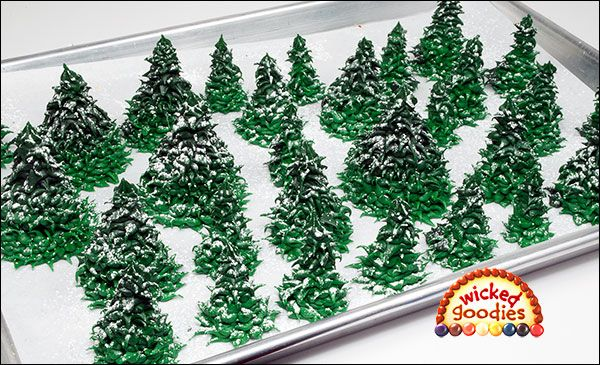 There are many different ways to make realistic looking fir trees for gingerbread houses.    Here is one way of making fir trees that involves piping in circles onto a piece of parchment or wax