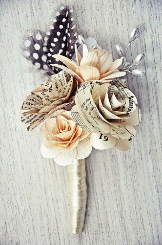Flowers: Wooden rose and layered lily made of birch wood shavings, vintage book page rose, music sheet paper rose Colors: Ivory, cream, vintage Accents: rice pearl sprays, guinea feathers Stem: Ivory