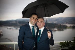 The classic Vancouver wedding shot - the umbrella is practically indespensible!  Photo by cakewalkmedia.ca