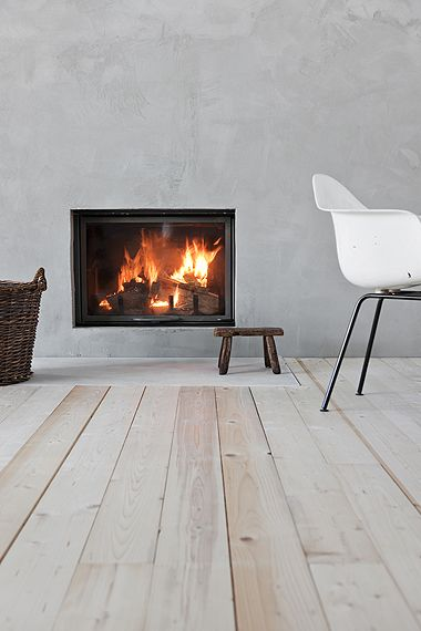 cozy austere, simple fireplace and chair