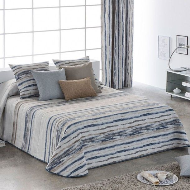 Colcha Bouti ATENAS de la firma Orian. Presenta un diseño a rayas difuminadas donde predominan los tonos en lila o en azul. Una bonita colección con la que vestirás tu cama de forma elegante y con las últimas tendencias en ropa de cama.