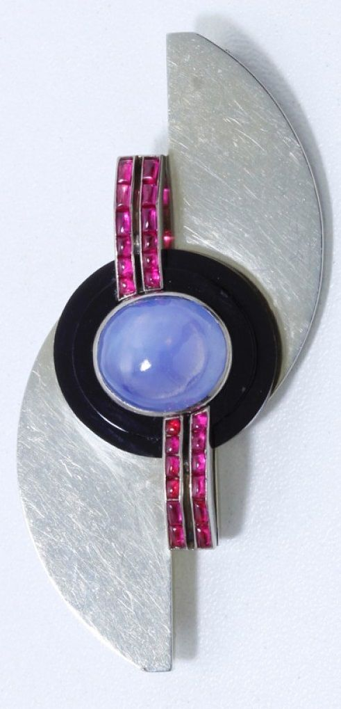 A beautiful and rare Art Deco brooch, French, circa 1930. Centring a round sapphire cabochon within an onyx frame, and further set with calibré rubies, mounted in gold. Illegible maker's mark. 6 x 3cm. Evocative of the work of great jewellers of the Art Deco period, such as Jean Després, Gérard Sandoz, Jean Fouquet, Raymond Templier, Jean Dunand and many others. #ArtDeco #brooch
