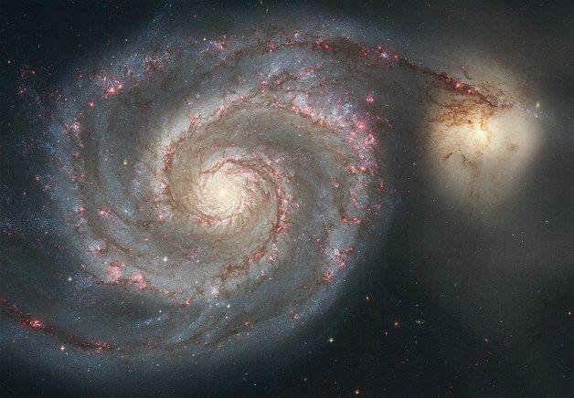 """Imagem: Galáxia Whirlpool (© NASA/ESA/AP) - Imagem feita pelo telescópio Hubble mostra a galáxia em espiral M51, conhecida como Whirlpool. As curvas sinuosas são formadas por estrelas, gás e poeira. À primeira vista, parece que uma galáxia menor, à direita, está puxando um dos """"braços"""" da M51. Mas uma interpretação da imagem dá conta que a galáxia menor está passando por trás da Whirlpool"""
