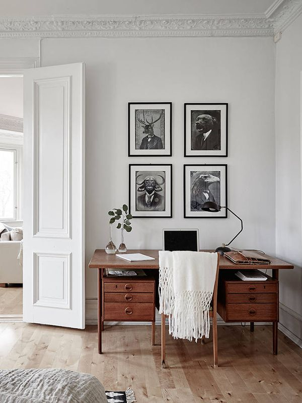 group of black and white art, all white walls and trim, wood floor. love the desk form: apartment Stadshem