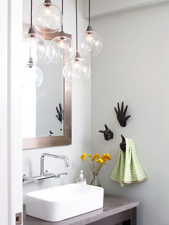 The organic shape of this blown-glass light fixture works well in the contemporary-style bathroom. Modern spaces can feel cold and be full of hard edges, but the round globes on the light fixture and the hand-shape towel hooks in this bathroom add a touch of playfulness.