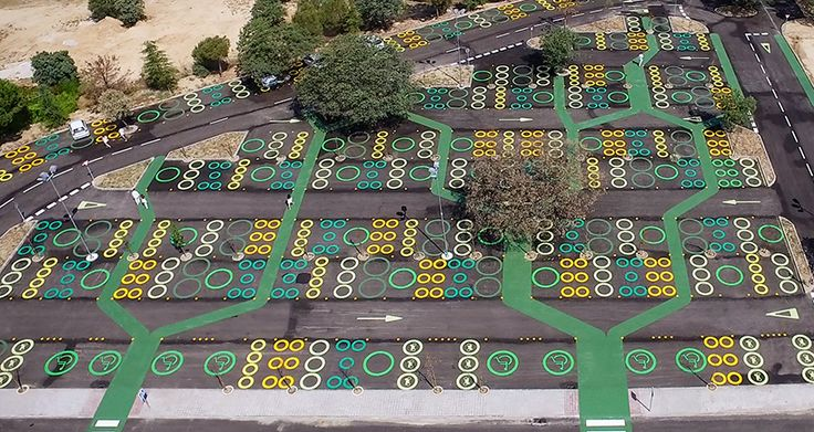 university parking lot in spain features colored circles and green pedestrian pathways
