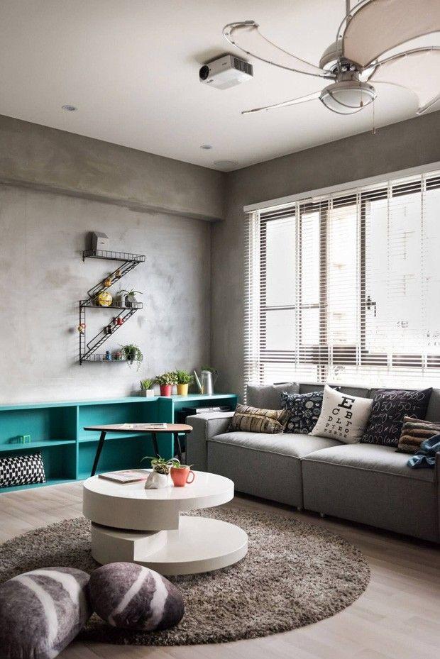 Decoração minimalista com pinceladas de referências lúdicas. Paredes de cimento alisado e piso de madeira clara com estante turquesa