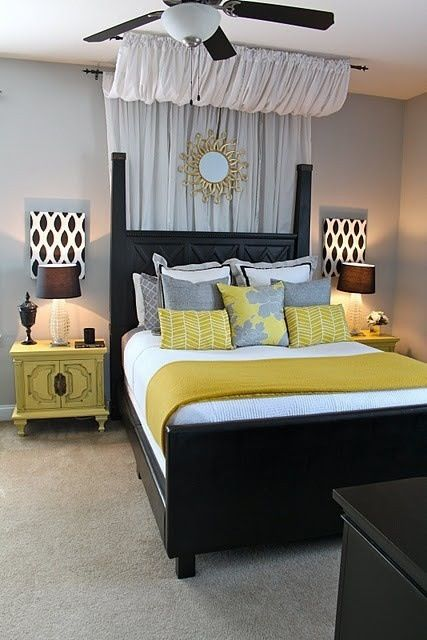 black bedframe with gray, yellow, and white bedding - same color scheme as mine. Like the colored end tables and matching patterned canvases.
