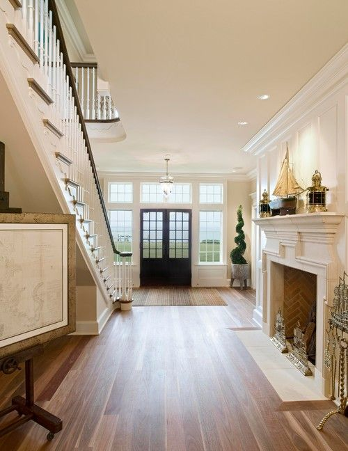 There is something grand, and a little Old World about the fireplace in the entry... Coastal design, and light an airy, but with a nod to tradition.