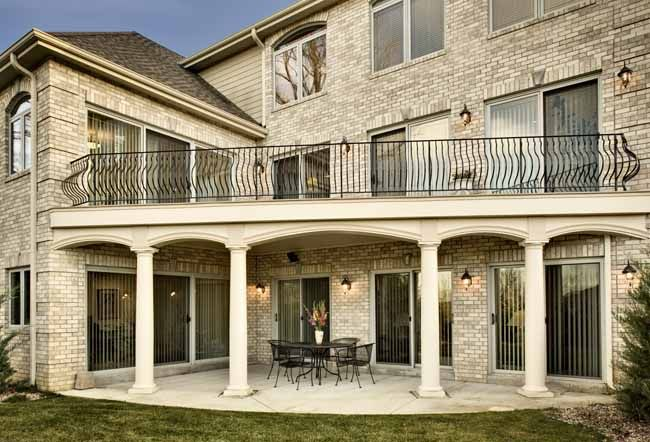 During this home remodel, the deck was built out 4 1/2 inches, and now has efficient drainage, and four tapered fiberglass columns, and curved wrought iron balusters.