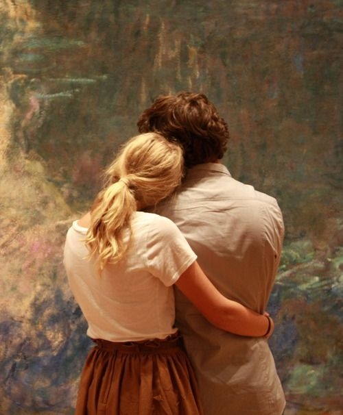 A couple admires the color and texture of Monet's Water Lilies at MoMA, New York