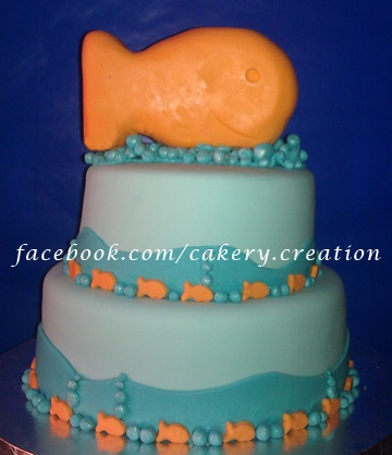 Gold Fish Cracker themed cake. Vanilla cake colored orange with pineapple filling. Fondant gold fish and rice krispie treat gold fish topper.