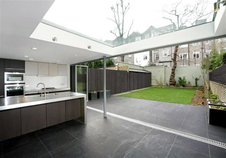 Modern extension to a listed terraced house in St Johns Wood, London. entire wall opens up to the garden and roof light brings in  light throughout the day.