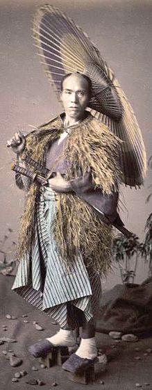 Samurai wearing a mino (straw rain cape) and holding an umbrella.