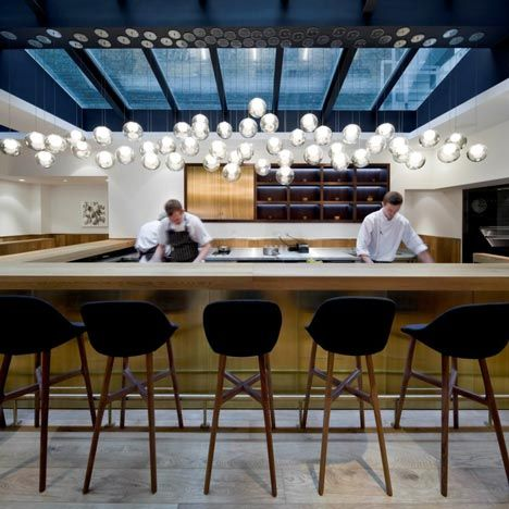 Clustered pendant lights are suspended over one of the open food and drink preparation areas of this London restaurant - Pollen St Local-by Chinese designers Neri