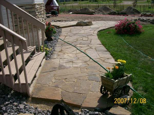 This country yard on an acreage looks much more at home with a dry-laid flagstone walkway from the gravel driveway to the front door. Picture compliments of Dream-yard.