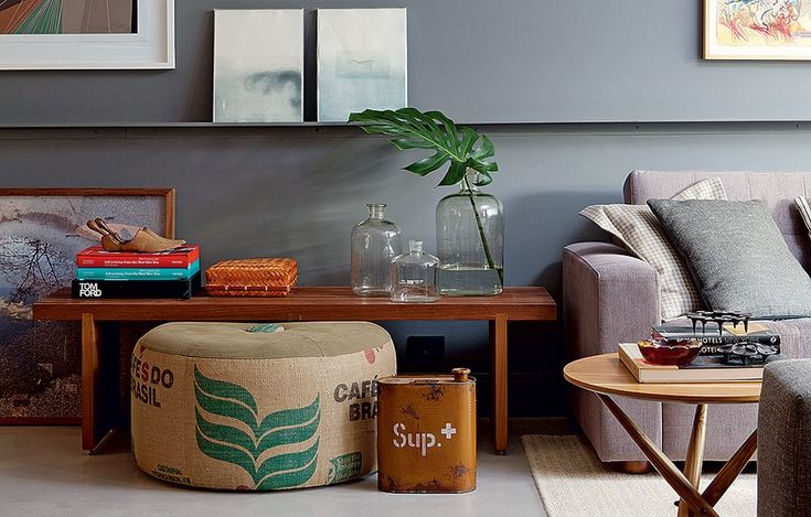 O pufe lembra as sacas de transporte de café e faz par com a lata de combustível antiga dando um ar inusitado à decoração do living