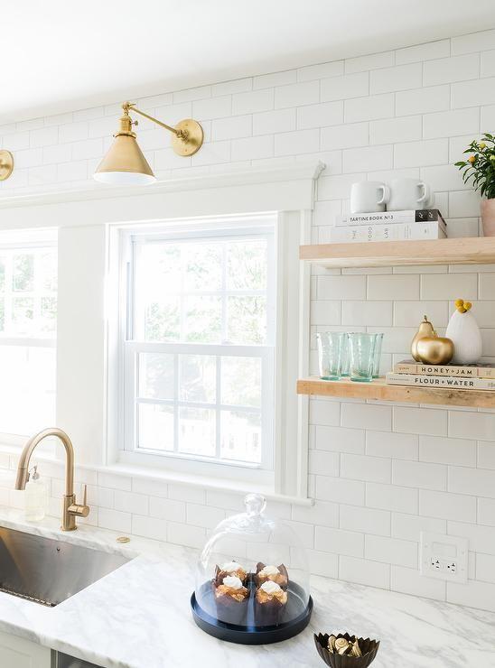 サブウェイタイルと明るいナチュラルな色味の無垢材の棚、真鍮の水栓金物や引き手とランプシェードのあるキッチン