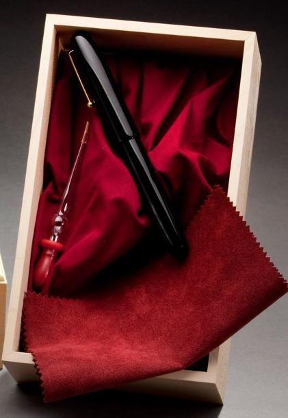 NAMIKI Modèle Empereur Noir. Stylo plume en laque noire, plume en or jaune 18k n°50. Le bouchon numéroté A4441. Etui de cuir noir présenté dans un écrin de bois clair sur un socle de présentation. Pipette… - Aguttes - 14/02/2015