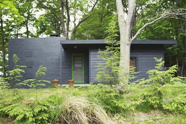 Sarah Sherman Samuel cabin exterior front: Remodelista Behr paint cracked pepper siding colour, mossy green door with black trim