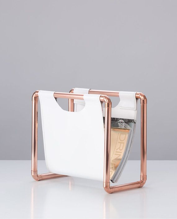 Industrial design, clear lines and simple elegance make the SKÍNA magazine rack a home accessoire which adapts to every environment. The hanger made of tough, white PVC canvas makes the ideal contrast to the flashy copper pipes and arranges for a balanced ensemble. With its height of ca 35 cm and a width of ca 39 cm MR 1 has enough space for a wide repertoire of magazines and newspapers.    The yellow seams serve as a small eye-catcher on the PVC hanger, which give a modern touch to the…