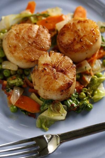 Sea scallops will caramelize deliciously if you follow a few simple caveats. Pat them dry thoroughly, sear them at a high temperature and don't flip them repeatedly. These have bacon in the mix.
