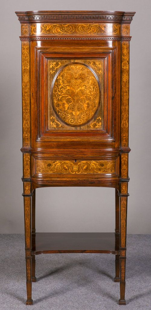 """A very fine inlaid rosewood cabinet from the workshops of top London cabinet makers """"Collinson and Lock"""". Of breakfront form with dentil cornice over a profusely inlaid frieze. The panelled door with a raised oval inlaid panel and below, a drawer with applied mouldings and further inlay of putti and grotesque mask. The whole standing on tall square tapering legs with applied mouldings, inlaid decoration and an under shelf"""