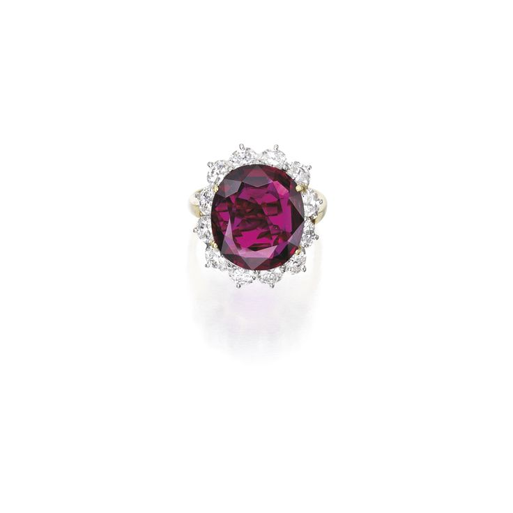 18 Karat Gold, Platinum, Ruby and Diamond Ring. Centering an oval-shaped ruby weighing 8.78 carats, framed by oval-shaped diamonds weighing approximately 2.75 carats, size 7¼.