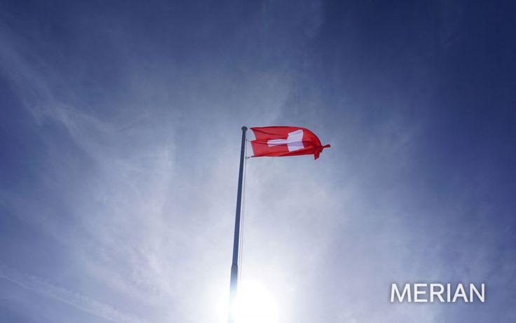 Nicht ganz komplementär flattert die Schweizer Flagge am blauen Himmel